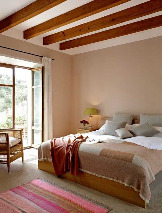 a bright modern bedroom with wooden beams, a stained bed, nightstands and a chair, bright printed textiles and a view