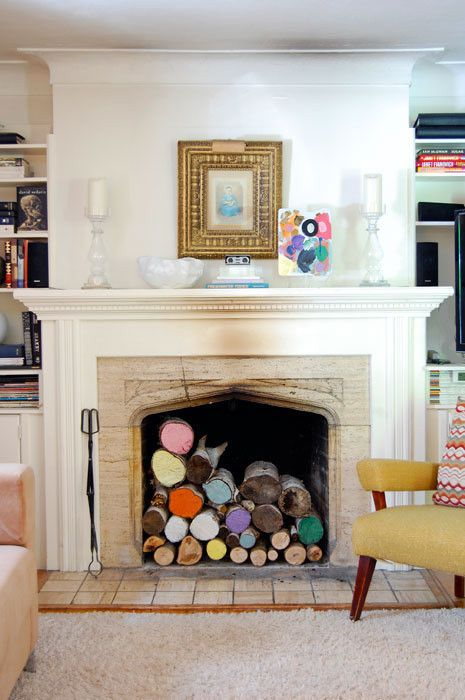 a bright nook with a built-in fireplace with colorful firewood inside, a neutral mantel, some candles, artworks and a bright chair