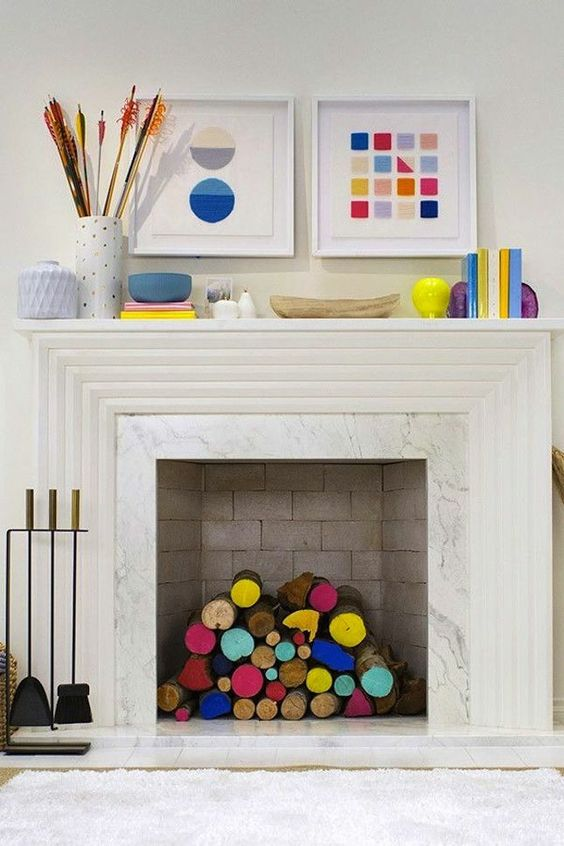 a bright space with a non-working fireplace and colorful firewood inside, with pretty books, vases and artworks is amazing