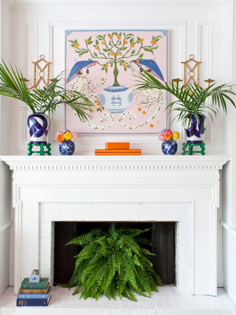 a bright space with a white fireplace and mantel, a colorful artwork, vases, blooms and greenery, a stack of books and a potted plant in the fireplace