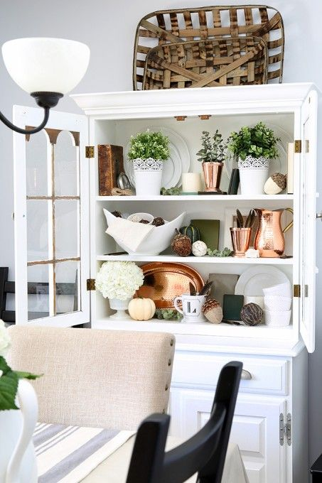 a buffet with hammered copper items, greenery and porcelain and blooms is a beautiful fall decoration to rock