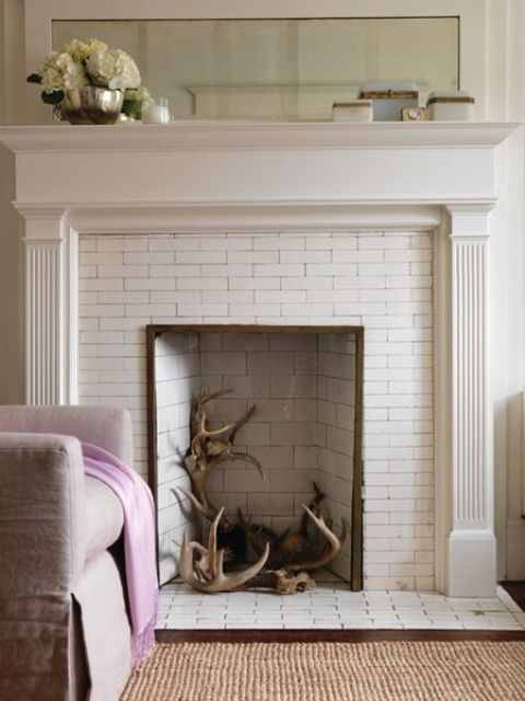 a built-in fireplace clad with white bricks is used to display antlers to give a slight woodland feel to the room