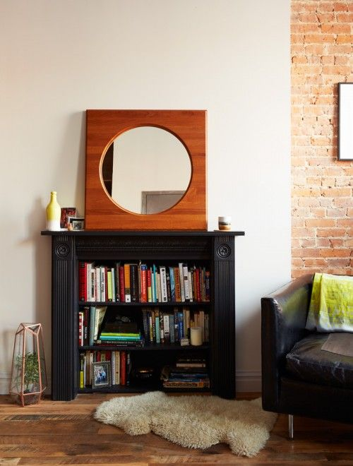 a built-in fireplace with a vintage black mantel and bookshelves built in for storage is a very creative and practical idea