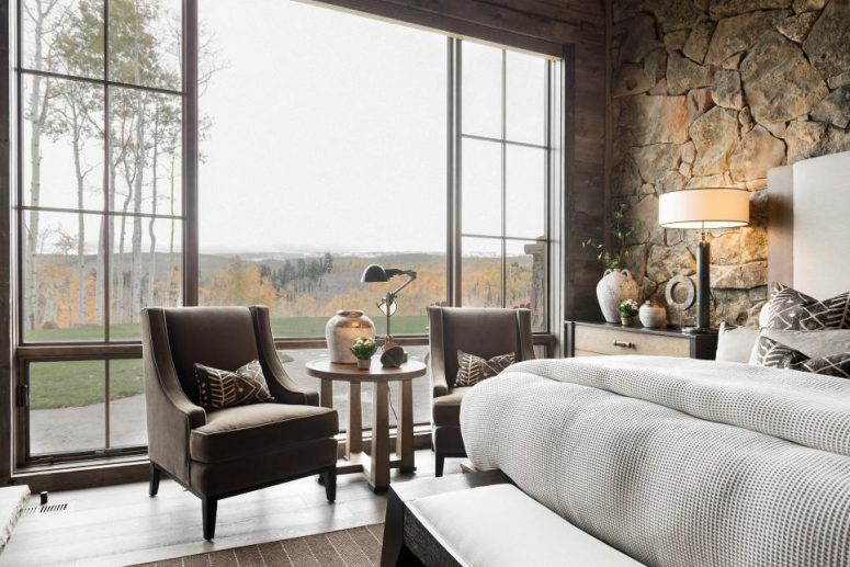 a cabin bedroom with stone walls, a bed, a dark stained bench, taupe chairs and printed pillows is welcoming
