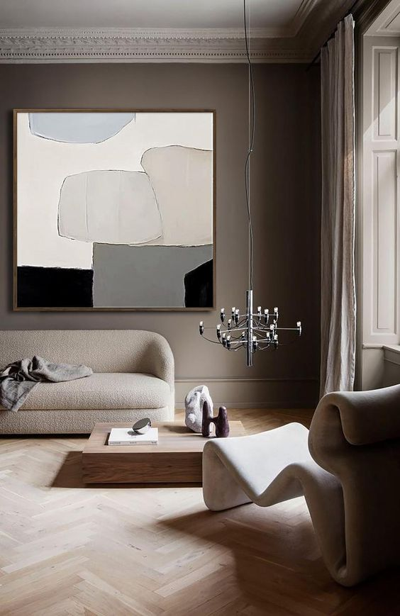 a catchy Japandi living room with taupe walls, sculptural furniture, a low coffee table and a bold chandelier and an artwork