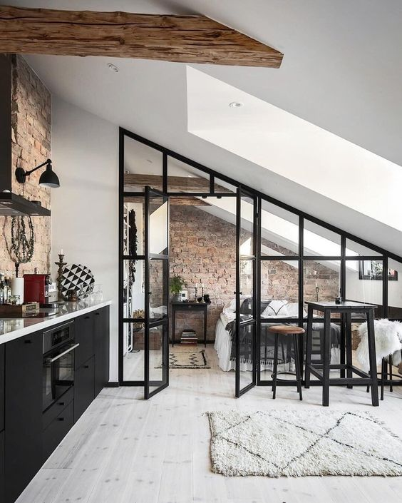 a catchy black attic kitchen with white countertops, an exposed brick backsplash, a wooden beams and a glass wall and doors leading to the bedroom