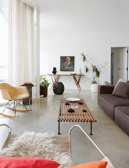 a catchy living room with a brown low sofa, a leather chair, a bench as a coffee table and a console table plus potted plants