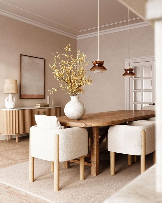 a chic Japandi dining room in neutrals with a lovely wooden slab credenza, a rounded table and neutral chairs, pendant lamps and a cool artwork