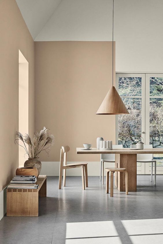 a chic Japandi dining space with tan walls, light-stained furniture, pendant lamps and a bench, cool views and pampas grass in a vase