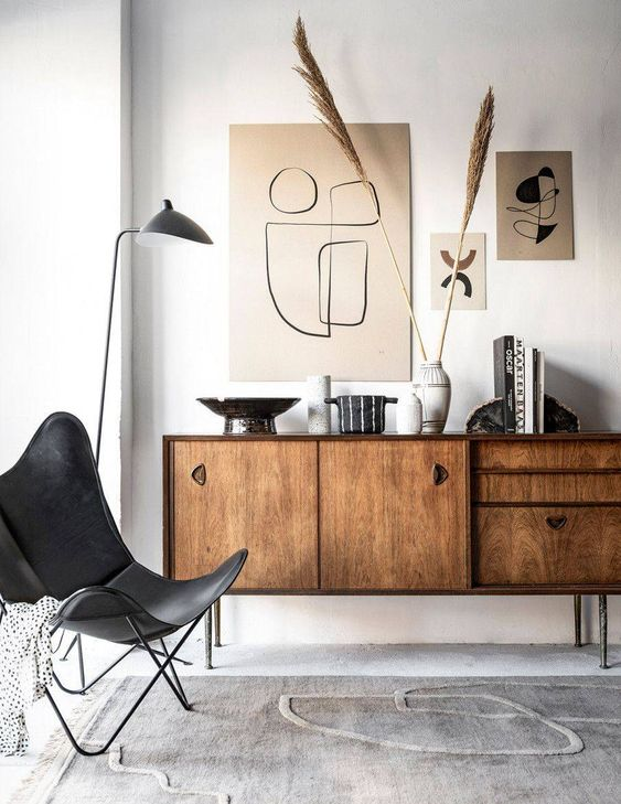 a chic Japandi living room with a rich-stained credenza, a black leather chair, a mini gallery wall and an arrangement of vases