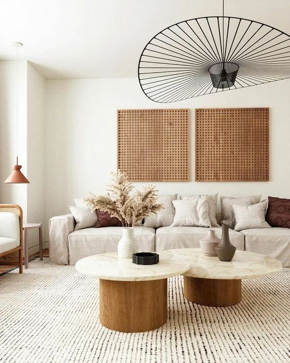 a chic Japandi living room with wooden slab artworks, a neutral low sofa, round tables and a cool round pendant lamp is amazing