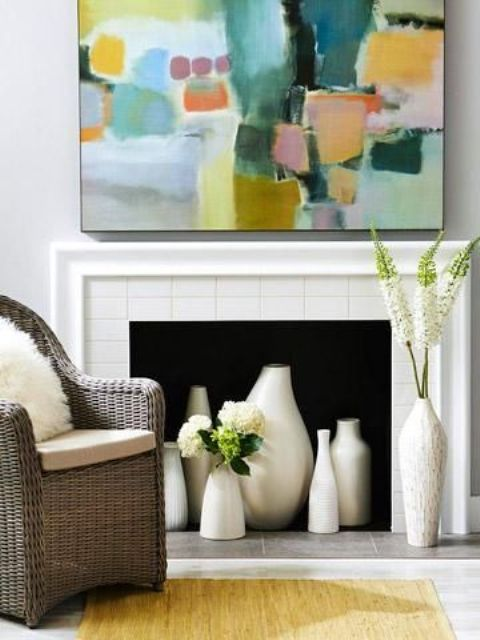 a chic and bright nook with a fireplace clad with tiles, lots of beautiful vases, a wicker chair and a colorful artwork