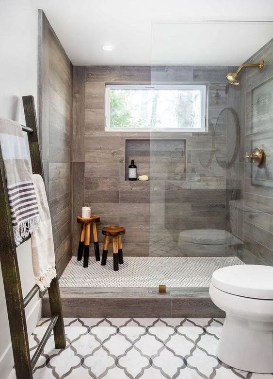 a chic bathroom clad with wood look tiles, with arabesque tiles on the floor, wooden stools, a ladder with towels and white appliances is cool