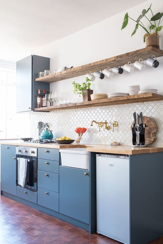 a chic blue kitchen with living edge floating shelves, butcherblock countertops and arabesque tiles on the backsplash