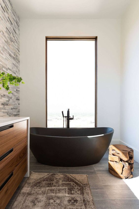 a chic farmhouse bathroom with a faux stone accent wall, a grey tile floor, a light-stained vanity, a black stone bathtub