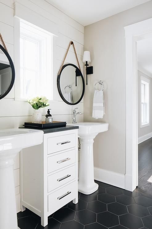 a chic farmhouse bathroom with black hex tiles, a wood plank wall, two pedestal sinks, a small storage cabinet and mirrors in black frames