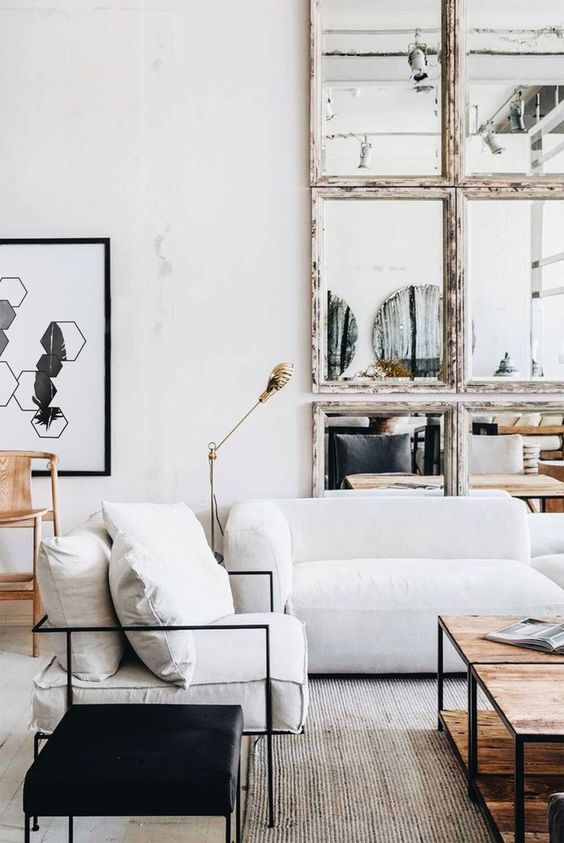 a chic living room with low seating furniture, a double wooden coffee table, a catchy mirror wall with shabby chic frames