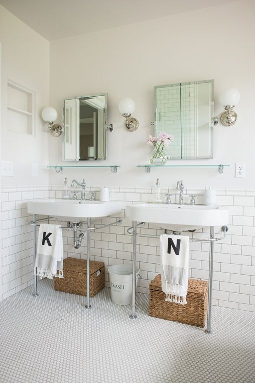 a chic modern bathroom done in neutrals, with a subway tile backsplash, glass shelves, console sinks, a double mirror and pretty sconces and penny tiles on the floor