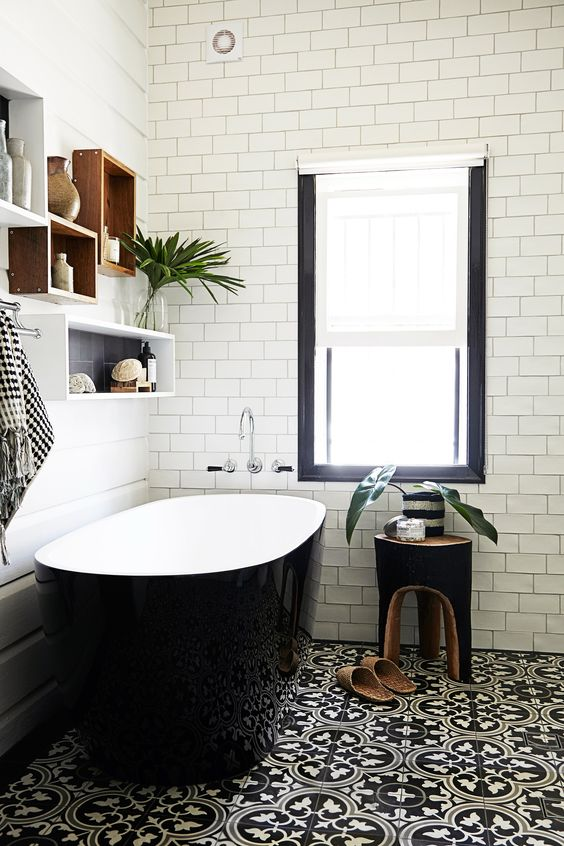 a chic modern bathroom with black patterned and white subway tiles, a sleek black bathtub and box shelves plus a black stool