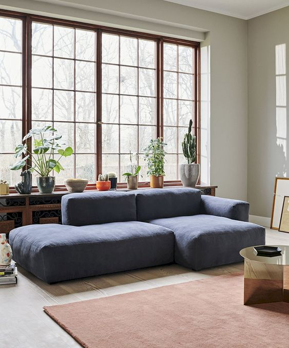 a chic modern living room with a blue low sofa, potted plants, a rust-colored rug, a mirror table is a very airy and cool space