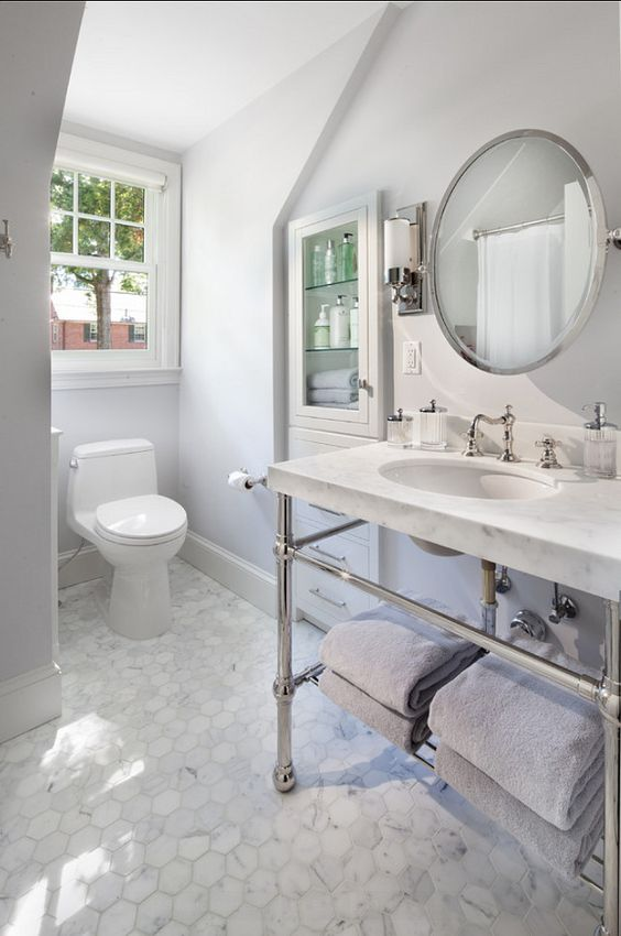a chic neutral bathroom with hexagon marble tiles, a console sink, a built-in storage unit, a round mirror and a window