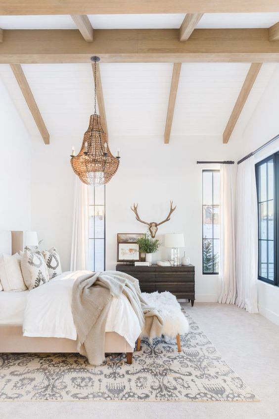 a chic neutral bedroom with wooden beams, a tan upholstered bed, neutral bedding, a crystal chandelier, a dark-stained dressser and a veiw of the lake