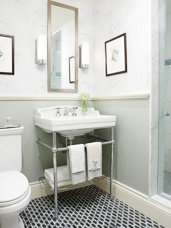 a chic powder room with wallpaper and green walls, a geo tile floor, a console sink and a narrow mirror plus some artworks