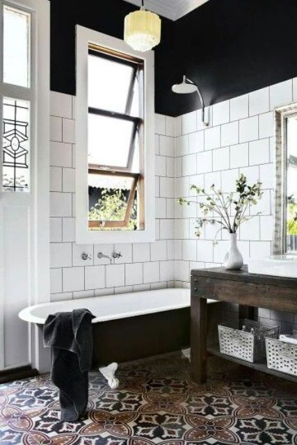 a chic vintage bathroom with patterned and square white tiles, a black clawfoot tub, a reclaimed wood vanity and pendant lamps