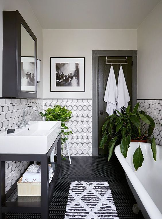 a chic vintage black and white bathroom with catchily shaped tiles and black penny ones, a console sink, a clawfoot tub and a black mirror cabinet