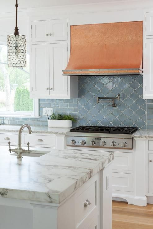 a chic vintage kitchen with white shaker cabients, a copper hood, white countertops and a blue arabesque and subway tiles on the backsplash