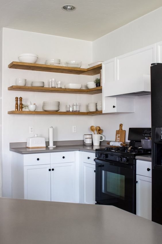 a clean white kitchen with shaker cabinets, black fixtures, grey countertops, light-stained corner floating shelves