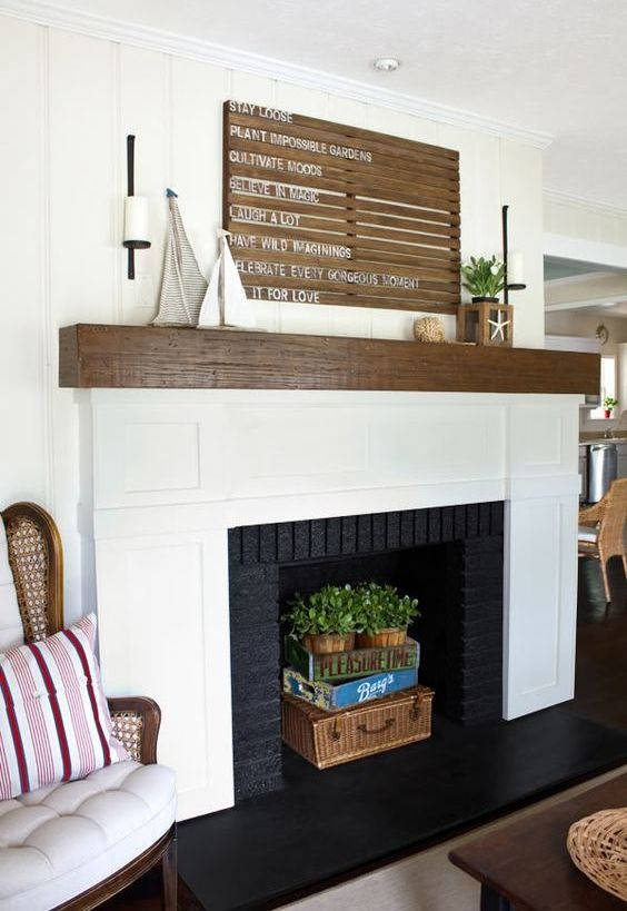 a coastal space with a built-in fireplace, a basket suitcase, books and potted greenery, a wooden sign, toy boats and a candle lantern