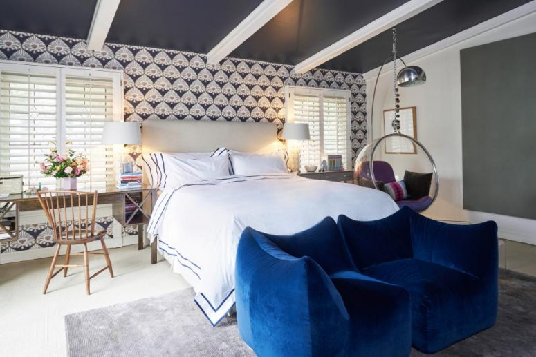 a colorful bedroom with an accent wall, a creamy bed, a bold blue sofa, desks as vanities and nightstands and a black ceiling