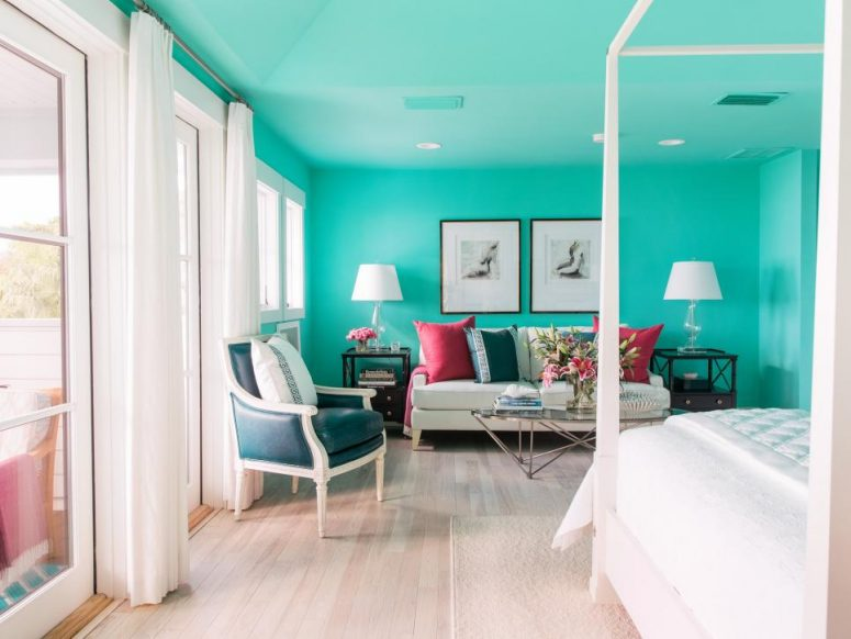 a colorful bedroom with turquoise walls and a ceiling, a white canopy bed, a creamy sofa with colorful pillows, a navy chair and a gallery wall