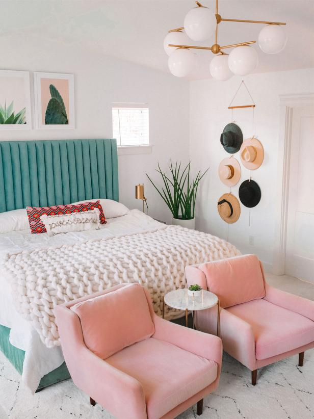 a colorful boho bedroom with a green upholstered bed, a gallery wall, pink chairs, hats on the wall as decor