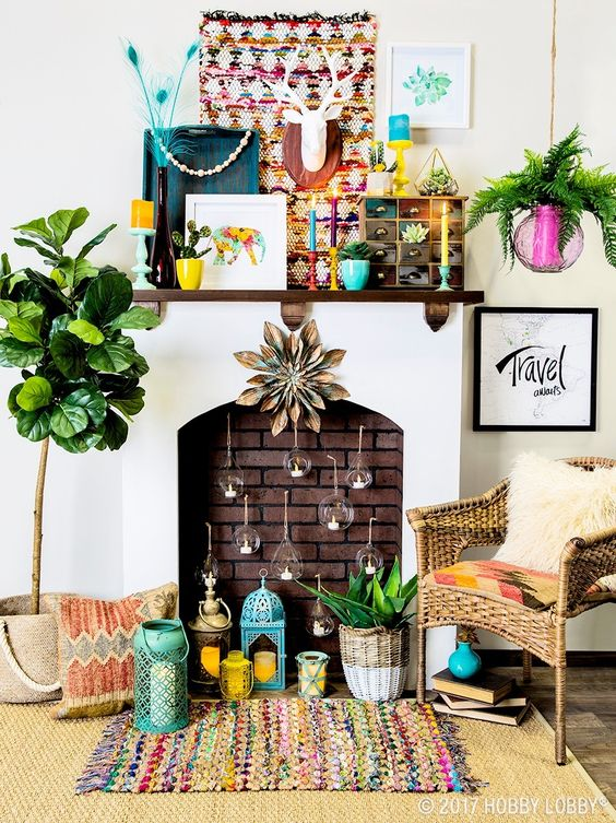 a colorful boho fireplace with candle bubbles inside, candle lanterns, potted plants, a colorful tapestry and bright planters