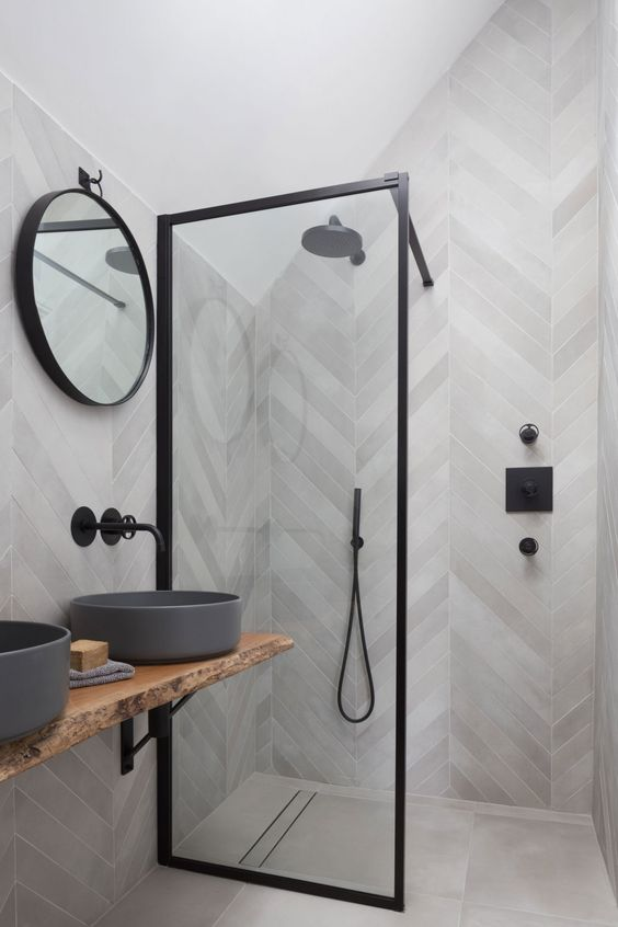 a contemporary bathroom clad with grey wood look tiles, with grey round sinks, a round mirror, a glass wall and black fixtures