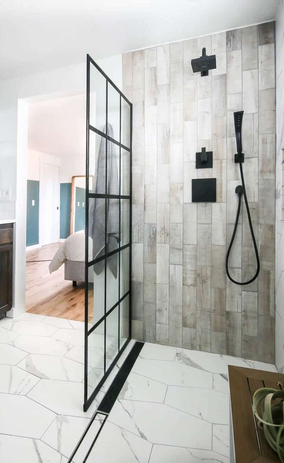 a contemporary bathroom clad with hex white stone tiles and wood look ones, with black fixtures and a glass framed wall is cool