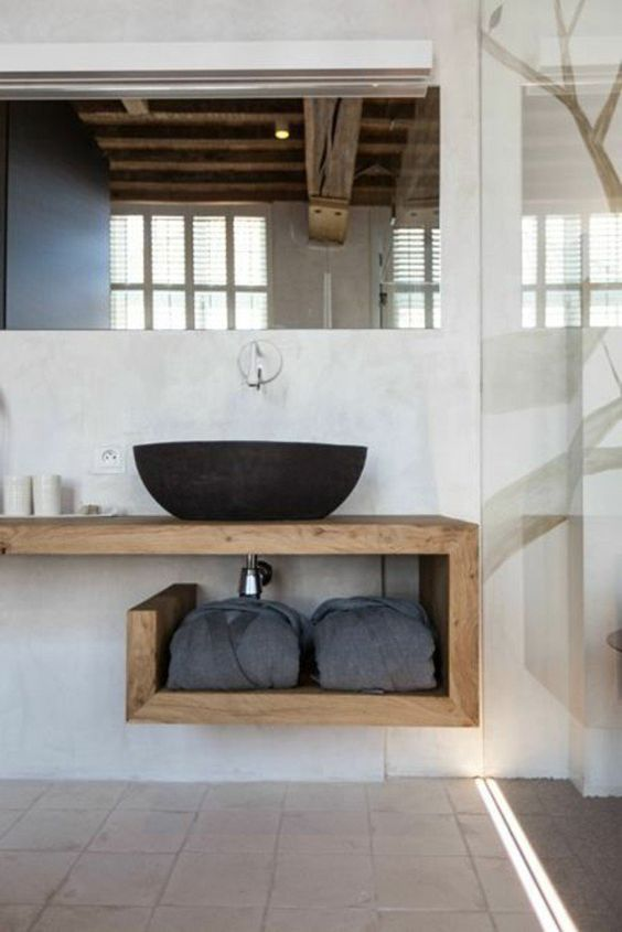 a contemporary bathroom clad with white and grey tiles, a plywood open vanity, a black stone vessel sink and a large mirror is cool