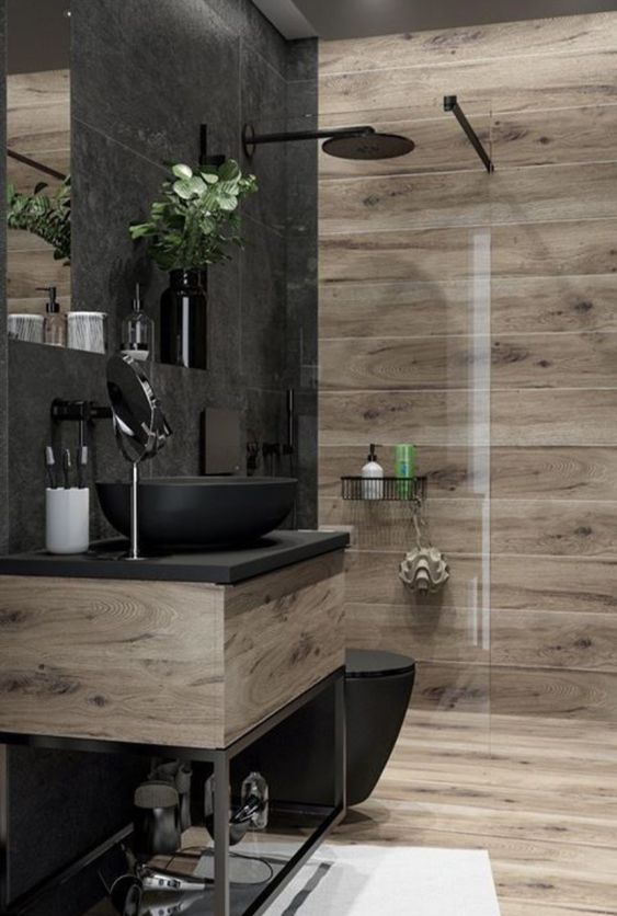 a contemporary bathroom clad with wood look and stone tiles, with a wooden and metal vanity, black appliances and black fixtures is stylish