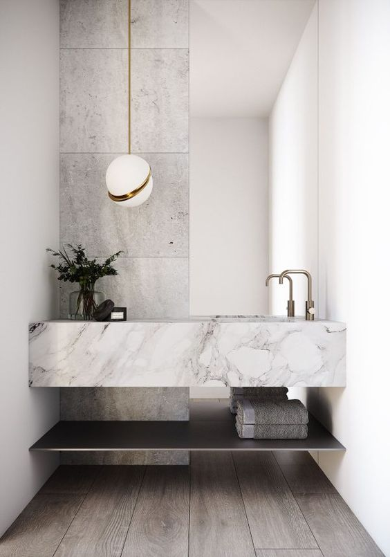 a contemporary bathroom in grey and white, with a grey floor, grey stone tiles, a floating stone sink and an open shelf, a cool pendant lamp is amazing