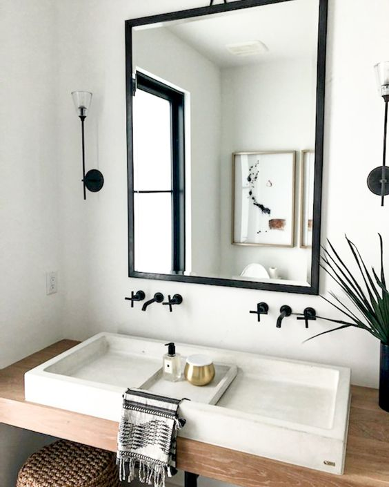 a contemporary bathroom with a floating vanity, a white stone vessel sink, a mirror in a black frame and black fixtures is cool