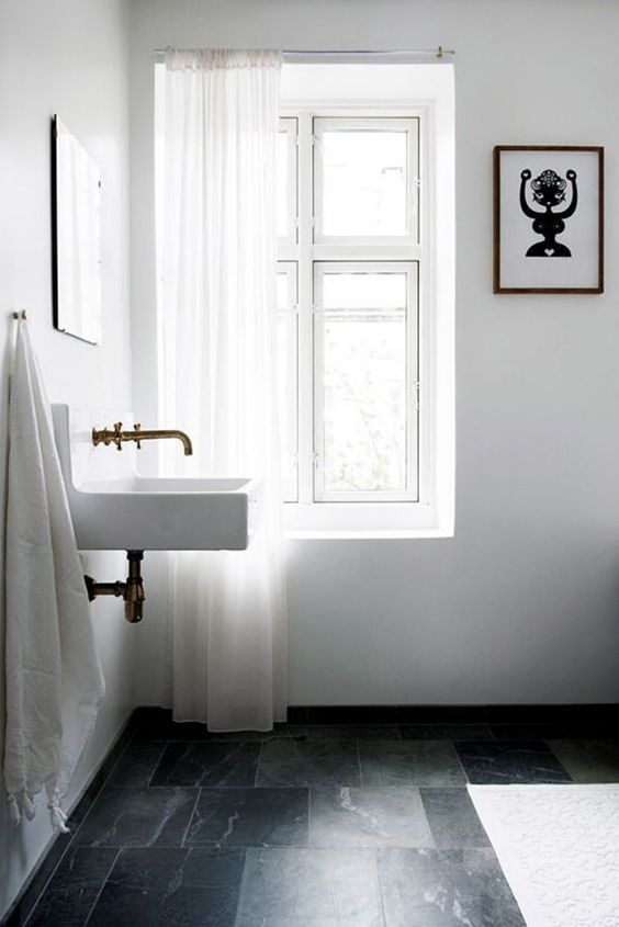 a contemporary bathroom with black stone tiles on the floor, a floating sink, vintage appliances and white textiles looks serene and airy