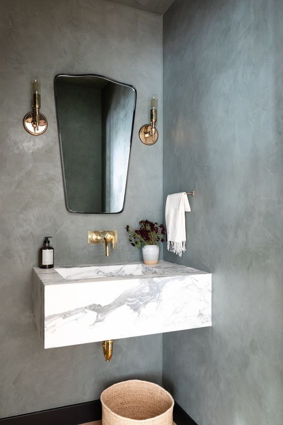 a contemporary bathroom with concrete walls, a floating stone sink, a catchy mirror, gold fixtures and brass sconces is very chic