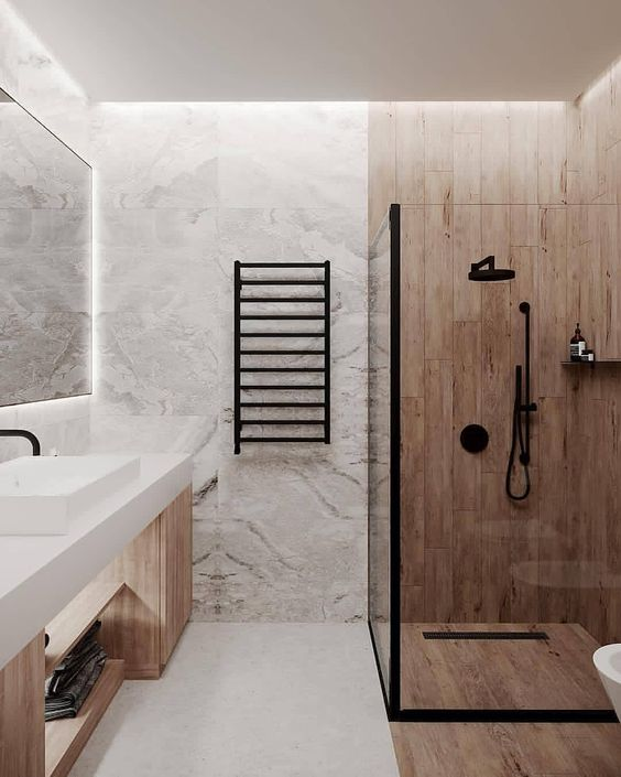 a contemporary bathroom with stone and wood look tiles, a wooden vanity, a white sink, black fixtures and built-in lights