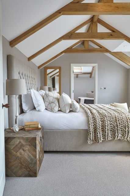a contemporary bedroom with light-stained wooden beams, a grey upholstered bed, neutral bedding, a wooden chest nightstand