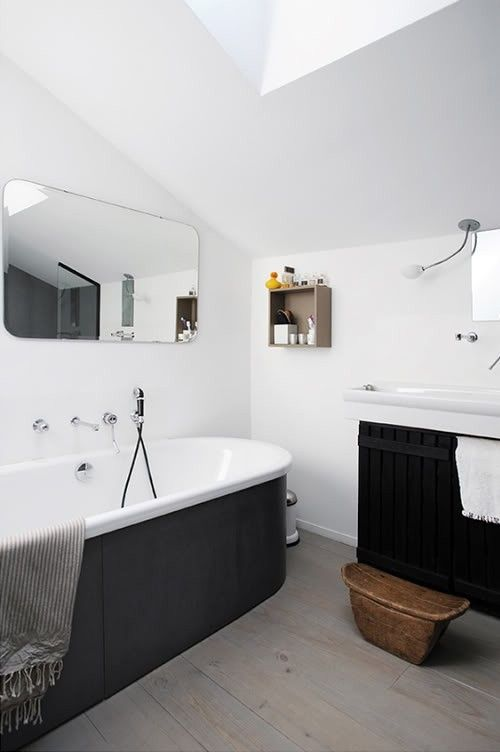 a contemporary black and white bathroom with white walls and laminate on the floor, a tub clad with black panels, a black paneled floating vanity and a rounded mirror