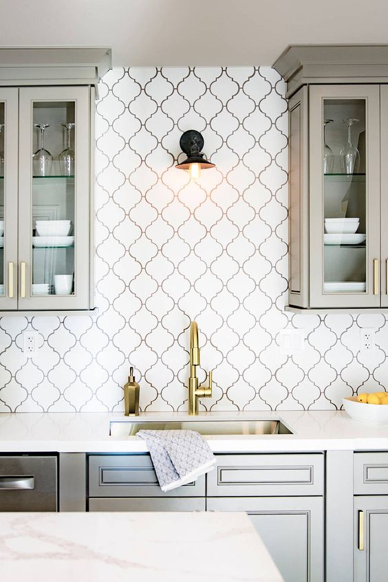 a contemporary light grey kitchen with glass cabinets, a white arabesque tile backsplash accented with black grout and gold fixtures