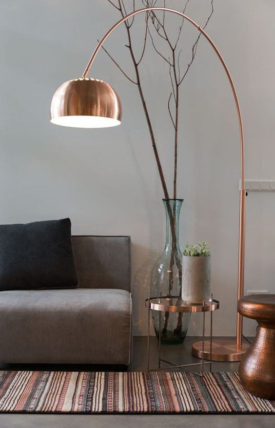 a contemporary living room with a bright rug, a copper hammered side table, a copper side table and a floor lamp for a fresh look