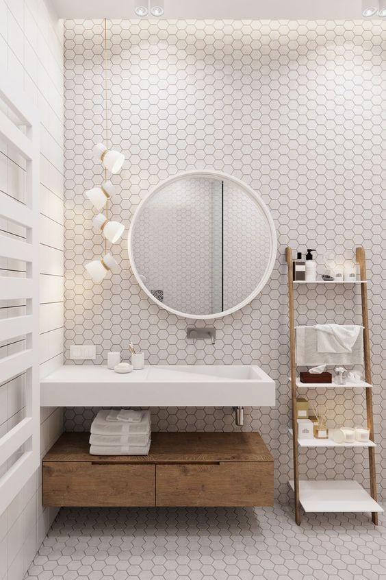a contemporary neutral bathroom clad with neutral hexagon tiles, with a floating sink, a small floating vanity, pendant lamps and a ladder as ashelving unit